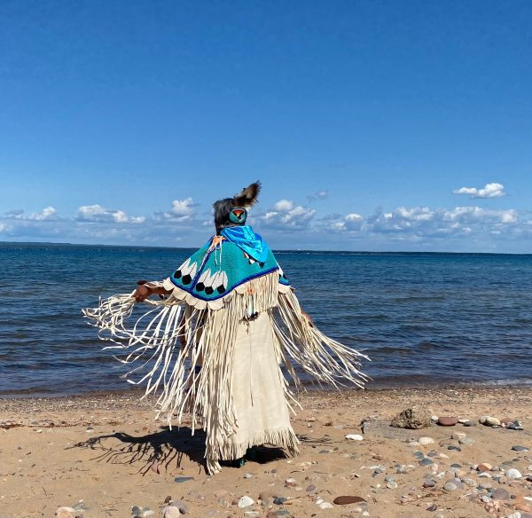 Beatrice Jackson in regalia facing the water on a beach